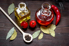 Carafes with oil and tomatoes on wooden background Stock Images