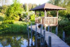 Caramanchão do jardim com um trajeto acima da lagoa Imagens de Stock