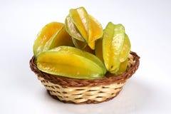 Carambola. Basket of ripe star fruit on white background stock photography