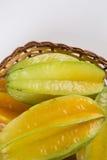 Carambola. Basket of ripe star fruit on white background stock images