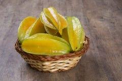 Carambola. Basket of ripe star fruit on wood royalty free stock photos