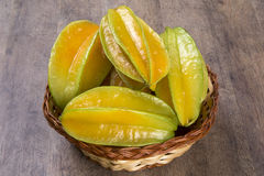 Carambola. Basket of ripe star fruit on wood royalty free stock image