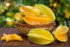 Carambola. Basket of ripe star fruit on wood royalty free stock photo