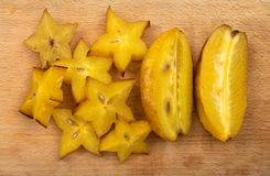 Carambola fruit on cutting board. Carambola or averrhoa fruit on cutting board. Starfruit top view Royalty Free Stock Image