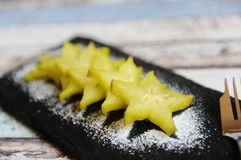 Carambola pieces served with icing sugar on a black slate plate royalty free stock image