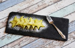 Carambola pieces served with icing sugar on a black slate plate stock photo