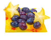 Carambola and plums on a plate isolated on white Royalty Free Stock Images
