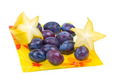 Carambola and plums on a plate isolated on white Stock Photo