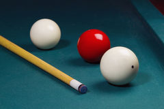 Carambole billiard balls. White and red carom balls with billiard cue on pocketless table Royalty Free Stock Images