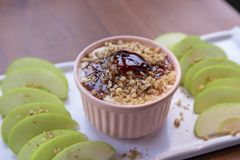 Caramel Apple Dip with nuts, caramel dressing and fresh apple slices. On wood stock photography
