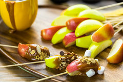Caramel Apples Toppings. Apple slices dipped in caramel and covered with different toppings Stock Photo
