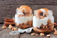 Caramel baked apple parfaits in mason jars on rustic wood Royalty Free Stock Photography