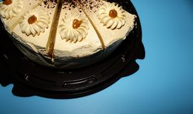 Caramel biscuit cake with cream on blue background royalty free stock images