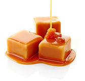 Caramel candies and caramel sauce. On a white background royalty free stock images