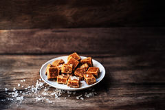 Caramel candies. Salted caramel pieces and sea salt macro. Royalty Free Stock Images