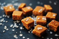 Caramel candies. Salted caramel pieces and sea salt macro. Stock Image
