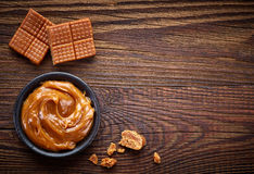 Caramel candies and sweet sauce. On wooden table, top view royalty free stock photo