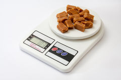 Caramel candies on white digital kitchen scale Stock Photo
