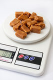 Caramel candies on white digital kitchen scale Royalty Free Stock Photography