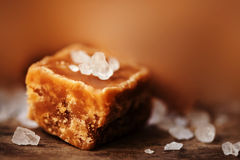 Caramel candy on brown  background macro. Salted caramel piece a Royalty Free Stock Photo