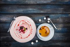 Caramel cheesecake with strawberry on the wooden background top view. Caramel cheesecake with strawberry with cup tea and cutlery on the wooden background top Royalty Free Stock Photo