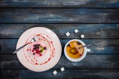 Caramel cheesecake with strawberry on the wooden background top view. Caramel cheesecake with strawberry with cup tea and cutlery on the wooden background top Stock Image