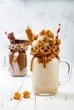 Caramel and chocolate crazy freakshake milkshakes with brezel waffles, popcorn, marshmallow, ice cream and whipped cream. royalty free stock images