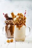 Caramel and chocolate crazy freakshake milkshakes with brezel waffles, popcorn, marshmallow, ice cream and whipped cream. Stock Photo