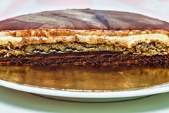 Caramel cream cake with nuts and chocolate layers. Homemade delicious dessert half sliced Stock Photography