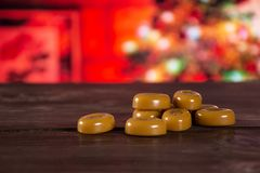 Caramel cream candy butterscotch with christmas tree behind. Lot of whole hard caramel cream candy butterscotch variety with christmas tree in red background stock photography