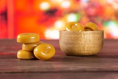 Caramel cream candy butterscotch with christmas tree behind. Lot of whole caramel cream candy butterscotch variety with wooden bowl with christmas tree in red stock image