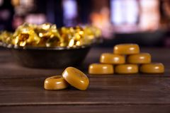 Caramel cream candy butterscotch with restaurant. Group of eight whole caramel cream candy butterscotch variety two in focus in old iron bowl with restaurant in stock photos