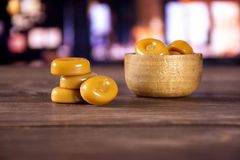 Caramel cream candy butterscotch with restaurant. Lot of whole caramel cream candy butterscotch variety with wooden bowl with restaurant in background stock images