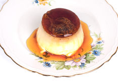Caramel cream dessert. Caramel dessert on a plate with flowers Stock Photos