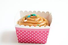 Caramel cupcake isolated on a white background. Caramel cupcake isolated on white in a pink and white polka dot holder Royalty Free Stock Photos