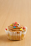 Caramel cupcake. On a wooden surface Stock Image