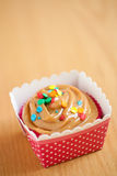 Caramel cupcake. On a wooden surface in a pink and white polka dot holder Royalty Free Stock Images