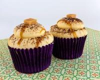 Caramel cupcakes on floral print Stock Image