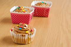 Caramel cupcakes. In pink and white polka dot holders on a wooden surface Royalty Free Stock Photography