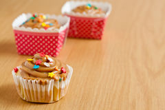 Caramel cupcakes. In pink and white polka dot holders on a wooden surface Royalty Free Stock Images