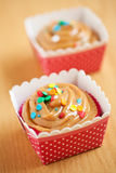 Caramel cupcakes. On a wooden surface in a pink and white polka dot holder Stock Photography