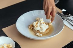 Caramel Custard with cream that topping with Popcorn by hand. Served in white plate.  stock photography