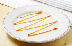 Caramel drizzle. On a plate Royalty Free Stock Photography