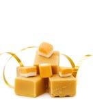 Caramel fudge and festive golden ribbon. Sweets Celebration - caramel fudge and golden ribbon. Isolated on white Stock Photos
