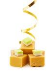 Caramel fudge and golden ribbon. Joy of food - caramel fudge with golden ribbon. Isolated on white background Royalty Free Stock Images