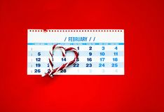 Caramel heart on the date of February 14 in the calendar on red background. royalty free stock photography