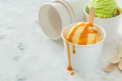 Caramel ice cream in paper cone. Marble background, copy space Royalty Free Stock Photography