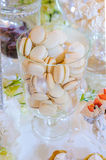 Caramel macaroons in a glass bell jar on a white wooden table. During wedding party royalty free stock photo
