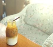 Caramel macchiato coffee in glass bottle with plastic straw stock images