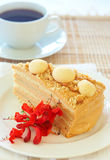 Caramel medovik cake. Slice of caramel Medovik cake made of honey and caramel cream, decorated with flowers with a cup of coffee Royalty Free Stock Photos
